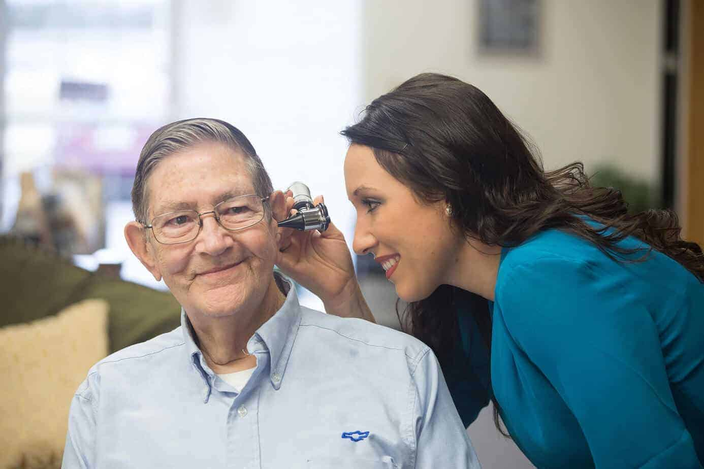 Candace inspecting a patient's ear with an otoscope